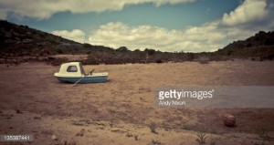 Small blue and white rowing boat in middle of dusty, dry dam, buoy lying on sand in foreground, plants on hills behind with clouds and blue sky in background. Tinted color, Kapteins Kop, Piketberg, Western Cape, South Africa